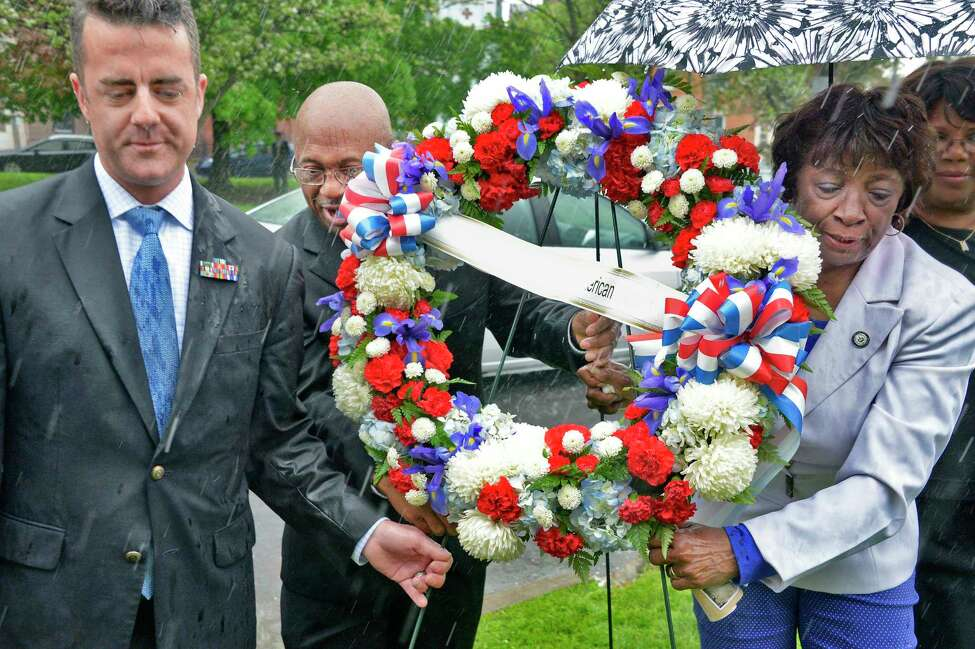 County legislature chairman Andrew Joyce, left, Command Sergeant Major Louis Wilson of the New York National Guard,(ret.) and Albany County Legislator Lucille M. McKnight place a wreath at the Sgt. Henry Johnson statue in Washington Park during a ceremony marking the 100th anniversary of Johnson's defeat of nearly two dozen German soldiers, an act that won him the Medal of Honor Tuesday May 15, 2018 in Albany,NY. (John Carl D'Annibale/Times Union)