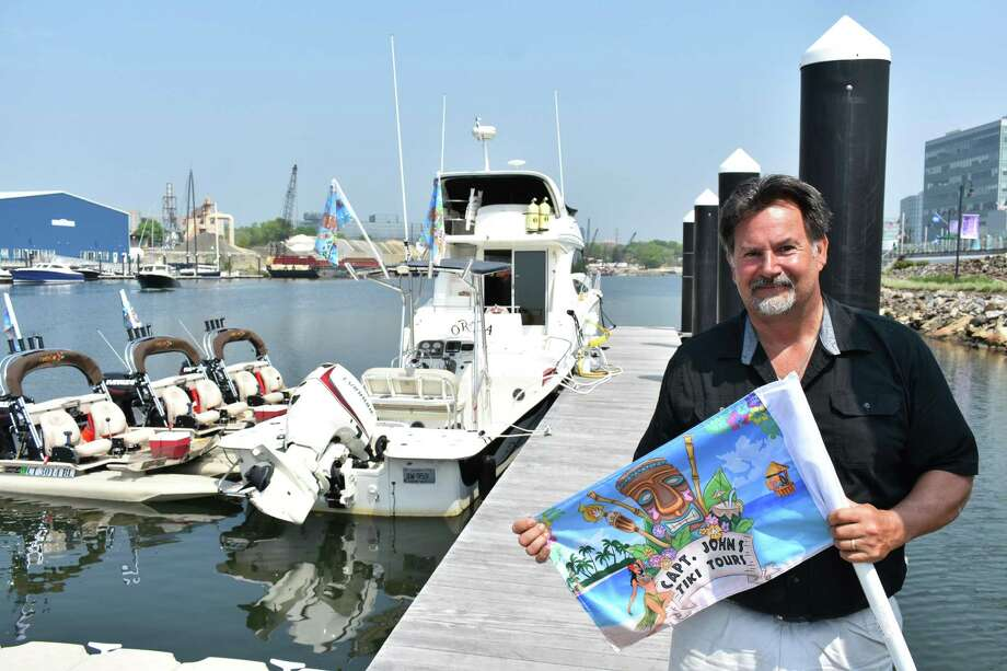 "John Davis on May 15, 2018, with ""Tiki Kat"" boats he began renting at Harbor Point in Stamford via his startup Captain John's Tiki Tours which will include floating tiki bars and yacht charters. Photo: Alexander Soule / Hearst Connecticut Media / Stamford Advocate"