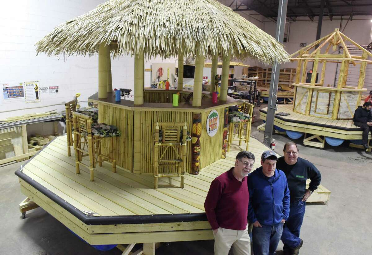 Bob Wolfgang, left, CEO of Cruisin Tikis, his son, Brian Wolfgang, center, COO of the company and Larry Davis, the founder and investor of the company, pose for a photo with one of their floating, powered tiki bars at the Cruisin Tikis manufacturing facility on Wednesday, March 15, 2017, in Colonie, N.Y. (Paul Buckowski / Times Union)