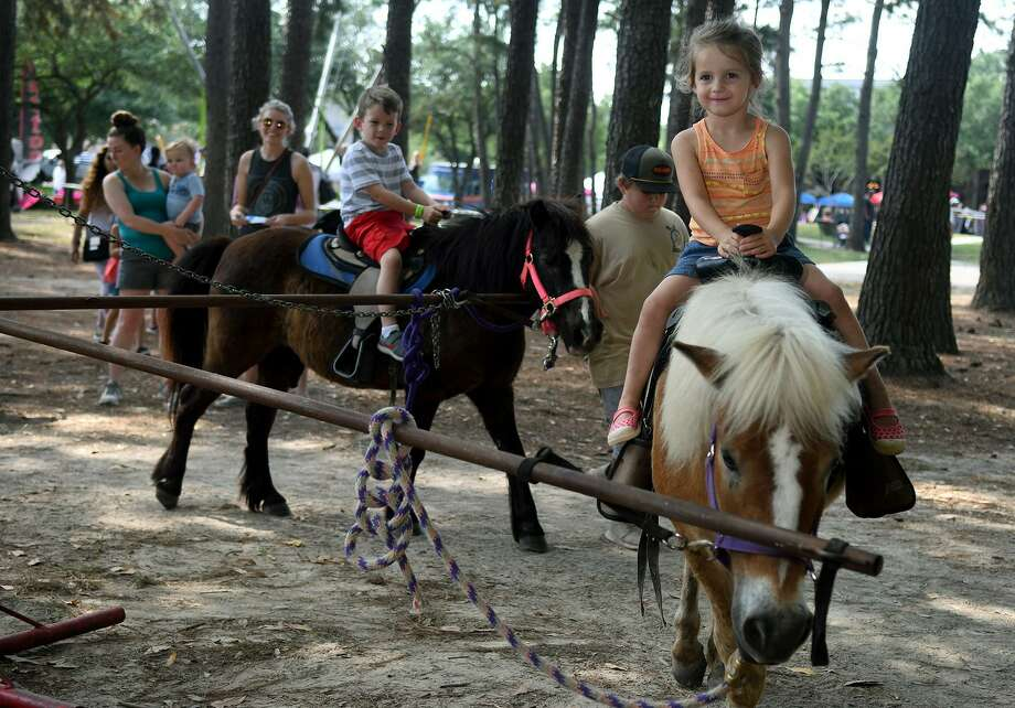 "Raerose Bettis, 4, right, of Kingwood, rides ""Blaze"" from EJC Farms in Hempstead, while Cooper Ellis, 5, left, a kindergartner at Southside Elem. in Cleveland, follows on ""Chocolate"" during the Kids Carnival and Food Truck Fest at Town Center Park in Kingwood on May 12, 2018. (Photo by Jerry/Freelance) Photo: Jerry Baker, Freelance / For The Chronicle / Freelance"