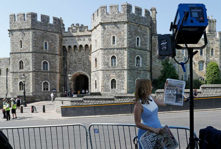 A television reporter for the US network CNN, holds up copies of today's British newspapers leading with a story of Meghan Markle's father Thomas Markle, opposite the Henry VII Gate of Windsor Castle in Windsor, west of London on May 15, 2018, as preparations get underway for the forthcoming Royal wedding. - Britain's Prince Harry and US actress Meghan Markle will marry on May 19 at St George's Chapel in Windsor Castle. Prince Harry and Meghan Markle's wedding this weekend was in turmoil Tuesday following reports her father may not attend after a paparazzi scandal, rocking the royal family's meticulous planning for the landmark occasion. Photo: ADRIAN DENNIS/AFP/Getty Images