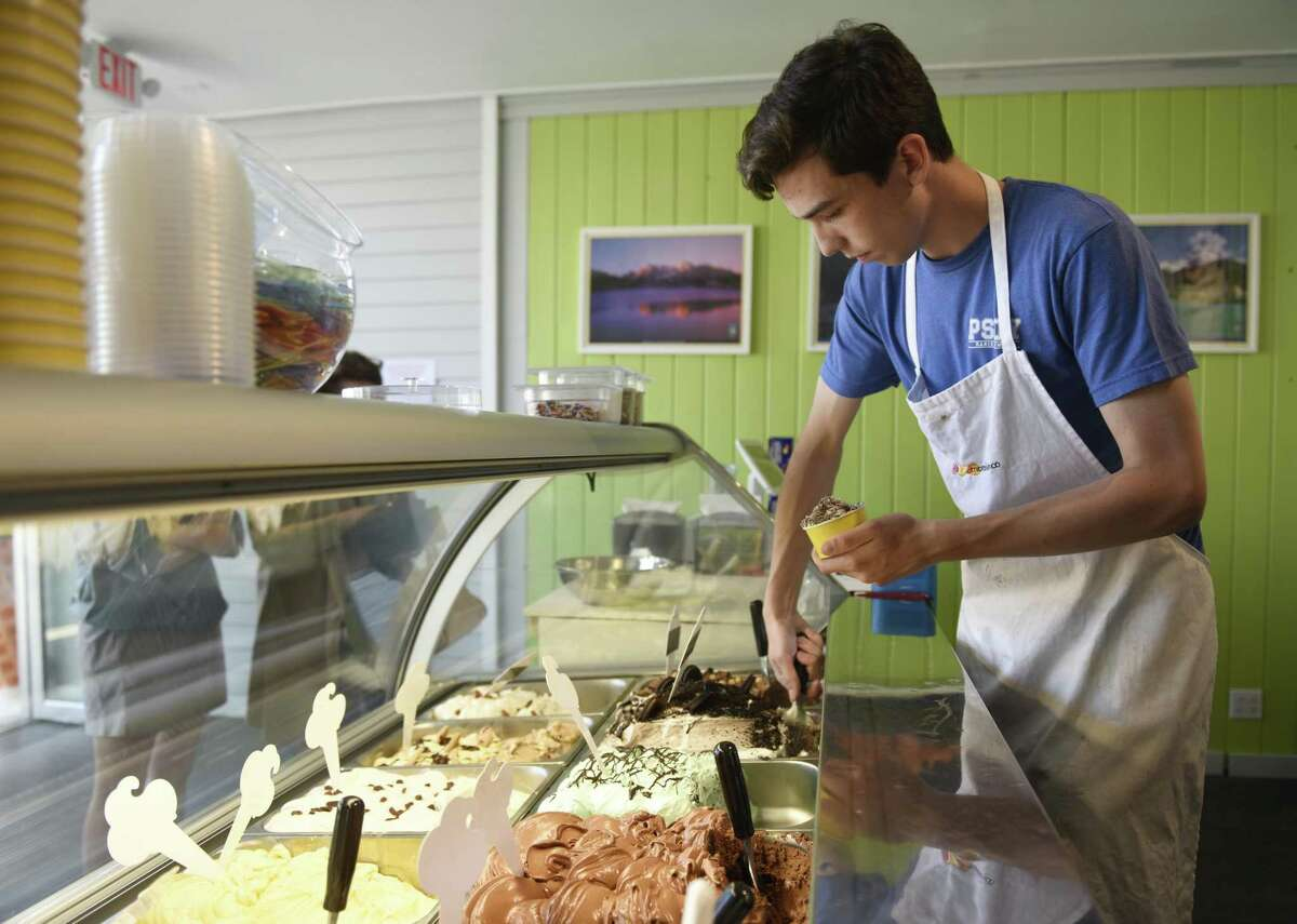 Employee Vittorio Marin scoops gelato behind the counter at Gelato & Cioccolato in the Cos Cob section of Greenwich, Conn. Tuesday, May 8, 2018. The new shop offers original Italian gelato from a family recipe born in northeastern Italy near Venice.