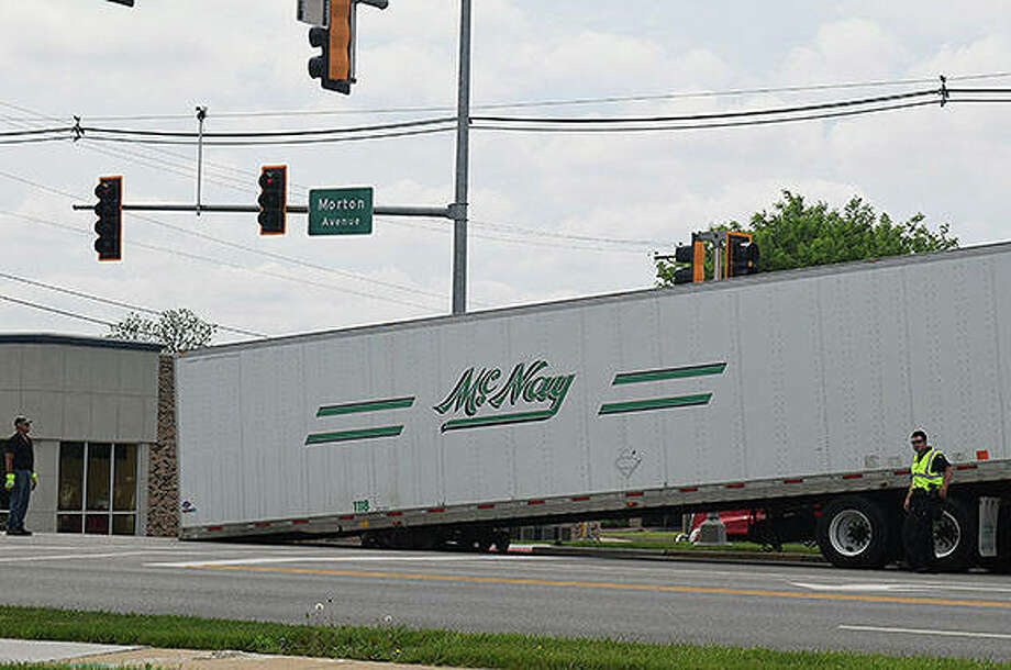 Police direct traffic around a semi-trailer that was left behind at Morton and Westgate avenues on Tuesday. There was a malfunction with the fifth wheel, also known as the trailer hitch, that caused it to fall off the truck. The trailer was towed away after a short period. Photo:       Audrey Clayton | Journal-Courier