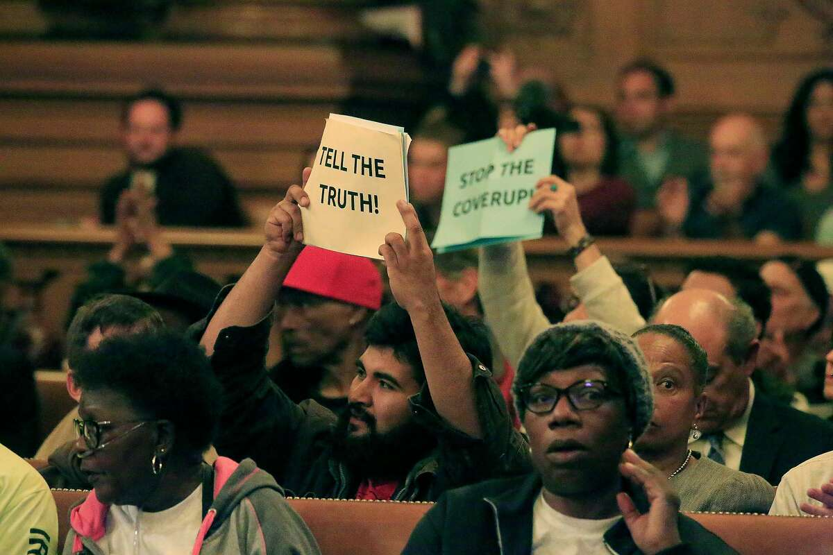 People hold up signs as they react during the Board of Supervisors' Land Use and Transportation Committee meeting during a hearing on the Hunters Point Shipyard clean-up on Monday, May 14, 2018 in San Francisco, Calif.