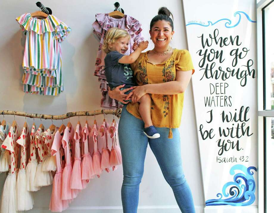 Dapper Darlings Owner Felicia Cumby poses with her 3-year-old son Jasper next to a painting that displays how much water entered their store. Over 5 feet of water went into Dapper Darlings. Photo: Kaila Contreras