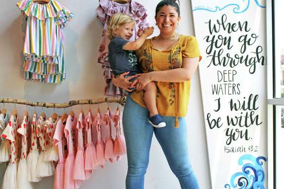 Dapper Darlings Owner Felicia Cumby poses with her 3-year-old son Jasper next to a painting that displays how much water entered their store. Over 5 feet of water went into Dapper Darlings.