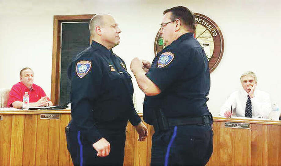 Outgoing Bethalto Police Chief Gregg Smock, right, pins regalia on his successor, Craig Welch, during a changing of the guard ceremony Monday night. Photo:       Alex Heeb | The Telegraph