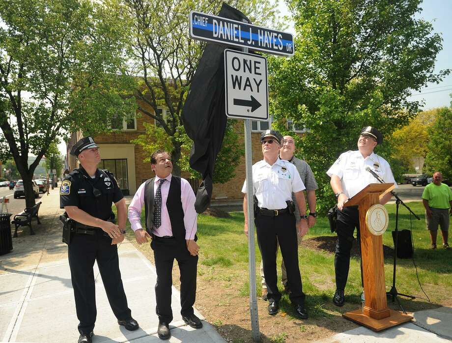 From left; Ansonia Officer Chris Kelley, Mayor David Cassetti, Chief Kevin Hale, retired Sergeant Randy Giusto, and Lieutenant Pat Lynch unveil a sign renaming Railroad Avenue to Chief Daniel J. Hayes Drive in Ansonia, Conn. on Tuesday, May 15, 2018. Hayes was the city's first police chief who was shot to death in the line of duty in 1880. Photo: Brian A. Pounds / Hearst Connecticut Media / Connecticut Post