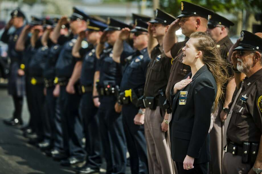 Midland County Sheriff's Office Administrative Secretary Amber Blevons sings the national anthem while Midland police officers salute the flag during a ceremony honoring fallen officers for Peace Officers Memorial Day on Tuesday, May 15, 2018 at the Midland Law Enforcement Center. (Katy Kildee/kkildee@mdn.net) Photo: (Katy Kildee/kkildee@mdn.net)