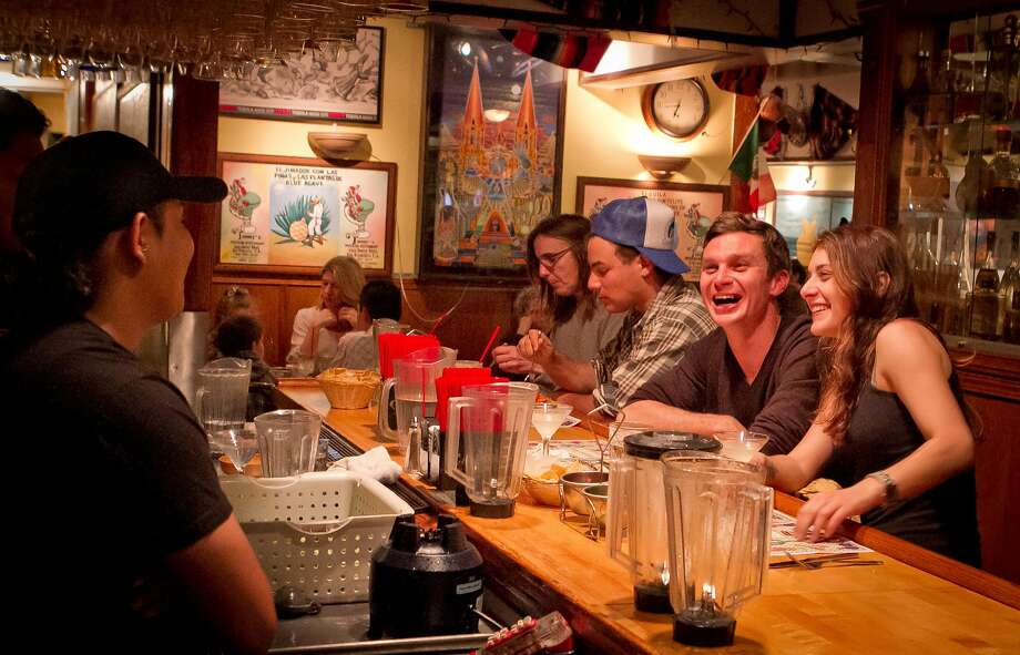 A couple has a laugh with bartender Greedy Balam at Tommy's Mexican Restaurant Photo: John Storey / The Chronicle