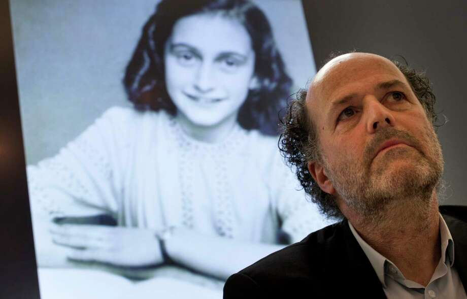 A picture of Anne Frank is projected as director Ronald Leopold of the Anne Frank Foundation listens during a press conference at the foundation's office in Amsterdam, Netherlands, Tuesday, May 15, 2018. Researchers have used digital photo editing techniques to uncover the text on two pages from Anne Frank's world famous diary that the teenage Jewish diarist had covered with brown masking paper, revealing risque jokes and an explanation of sex and prostitution. (AP Photo/Peter Dejong) Photo: Peter Dejong / AP 2018