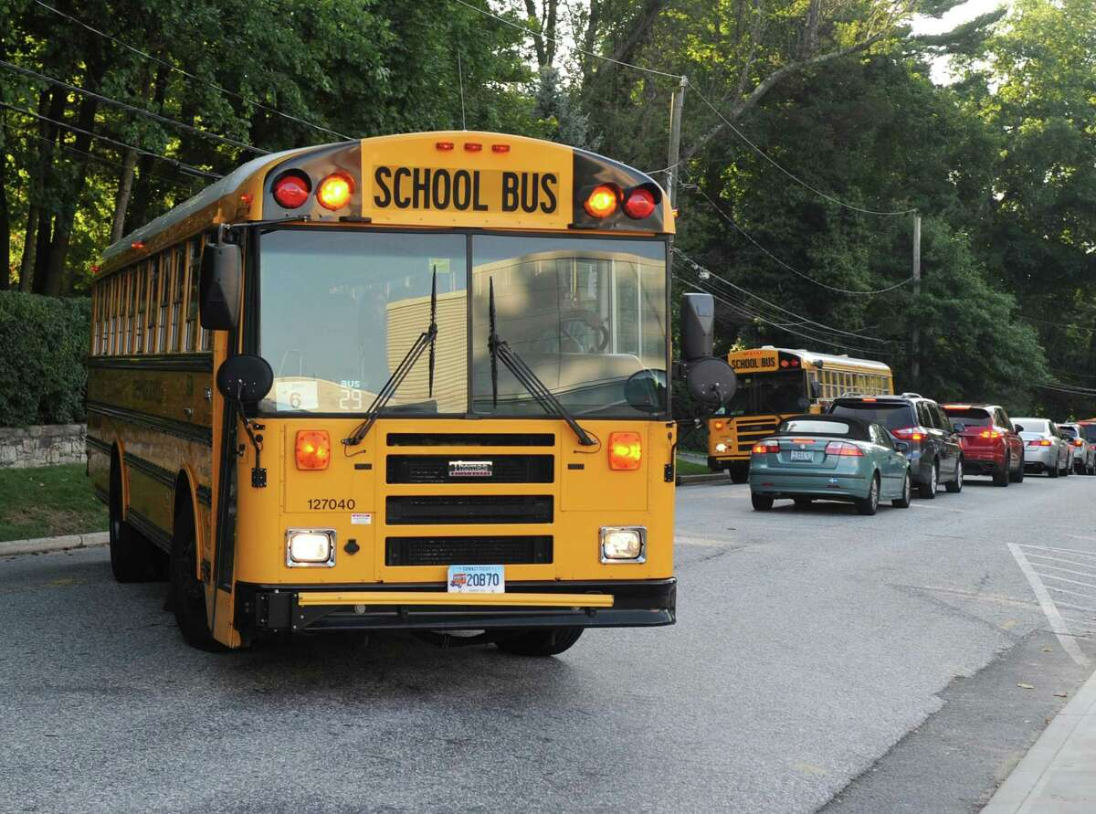 A school bus turns into Greenwich High School as a long line of cars wait to leave on Aug. 31, the first day of the 2017-2018 school year.