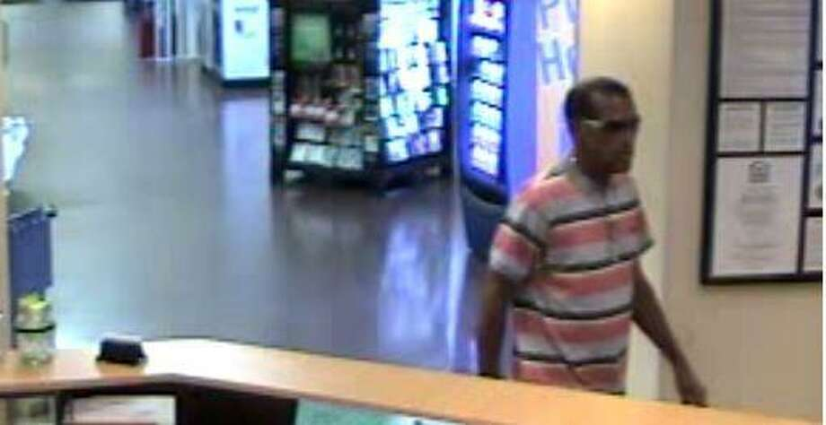 The suspect is believed to be an African American male in his early 50's at a height of approximately 5'10. He was wearing a striped shirt, blue jeans, black sneakers, dark sunglasses with a gray tint and a silver chain necklace. Photo: Woodforest National Bank Surveillance Footage