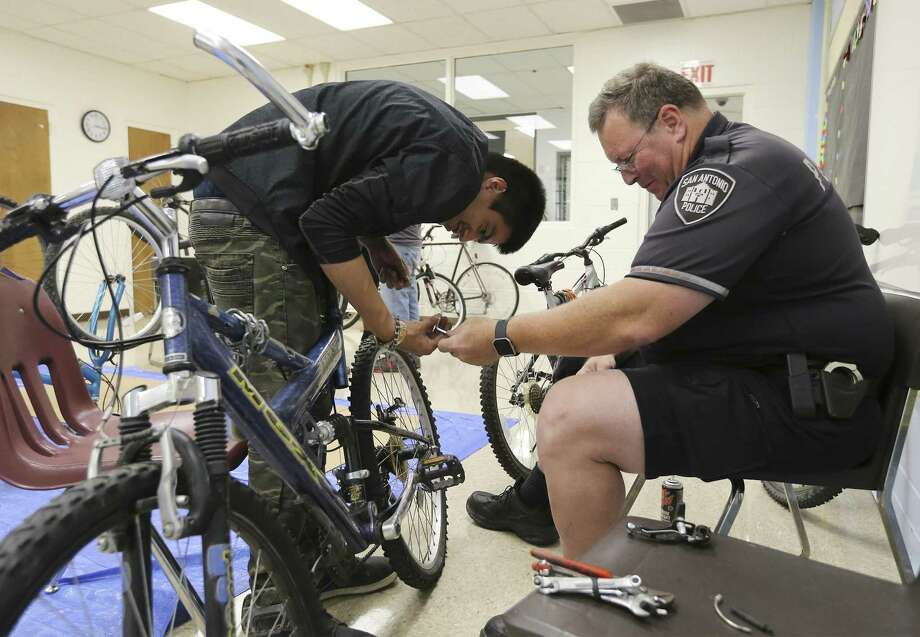 SAPD Bike Patrol Officer Steve Bazany (right) works with Paul Perez on bicycle brakes as Edgewood ISD and San Antonio police partnership to teach special needs students how to rebuild and repair a bicycle. For about the past four weeks at the Edgewood ISD Family Service Center, special needs individuals, like Perez, have been working with SAPD Bike Patrol officers to learn how to repair bicycle brakes, change out gears or fix a flat tire as part of the school district's 18-plus Transitional Program. The class is held twice a week for about 90 minutes. The bicycles are donated from the SAPD property room according to Bazany. The ultimate goal of the program is to help individuals with special needs to acquire job and life skills.  (Kin Man Hui/San Antonio Express-News) Photo: Kin Man Hui, Staff / San Antonio Express-News / ©2018 San Antonio Express-News