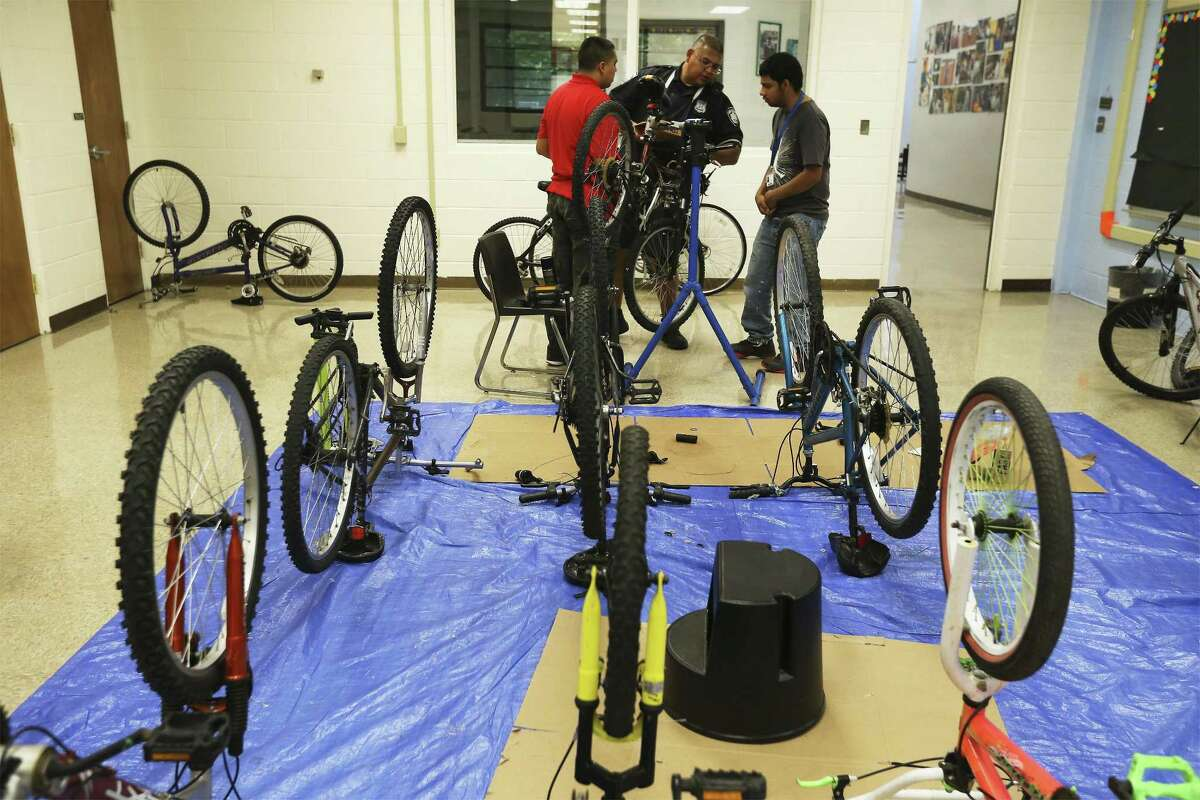 SAPD Bike Patrol Officer Ian Garcia works with Justin Avila (right) and Robert Garcia (left) on repairing a bicycle as Edgewood ISD and San Antonio police partnership to teach special needs students how to rebuild and repair bicycles. For about the past four weeks at the Edgewood ISD Family Service Center, special needs individuals have been working with SAPD Bike Patrol officers Steve Bazany and Ian Garcia in learning how to repair bicycle brakes, change out gears or fix a flat tire as part of the school district's 18-plus Transitional Program. The class is held twice a week for about 90 minutes. The bicycles are donated from the SAPD property room according to Bazany. The ultimate goal of the program is to help individuals with special needs to acquire job and life skills. (Kin Man Hui/San Antonio Express-News)