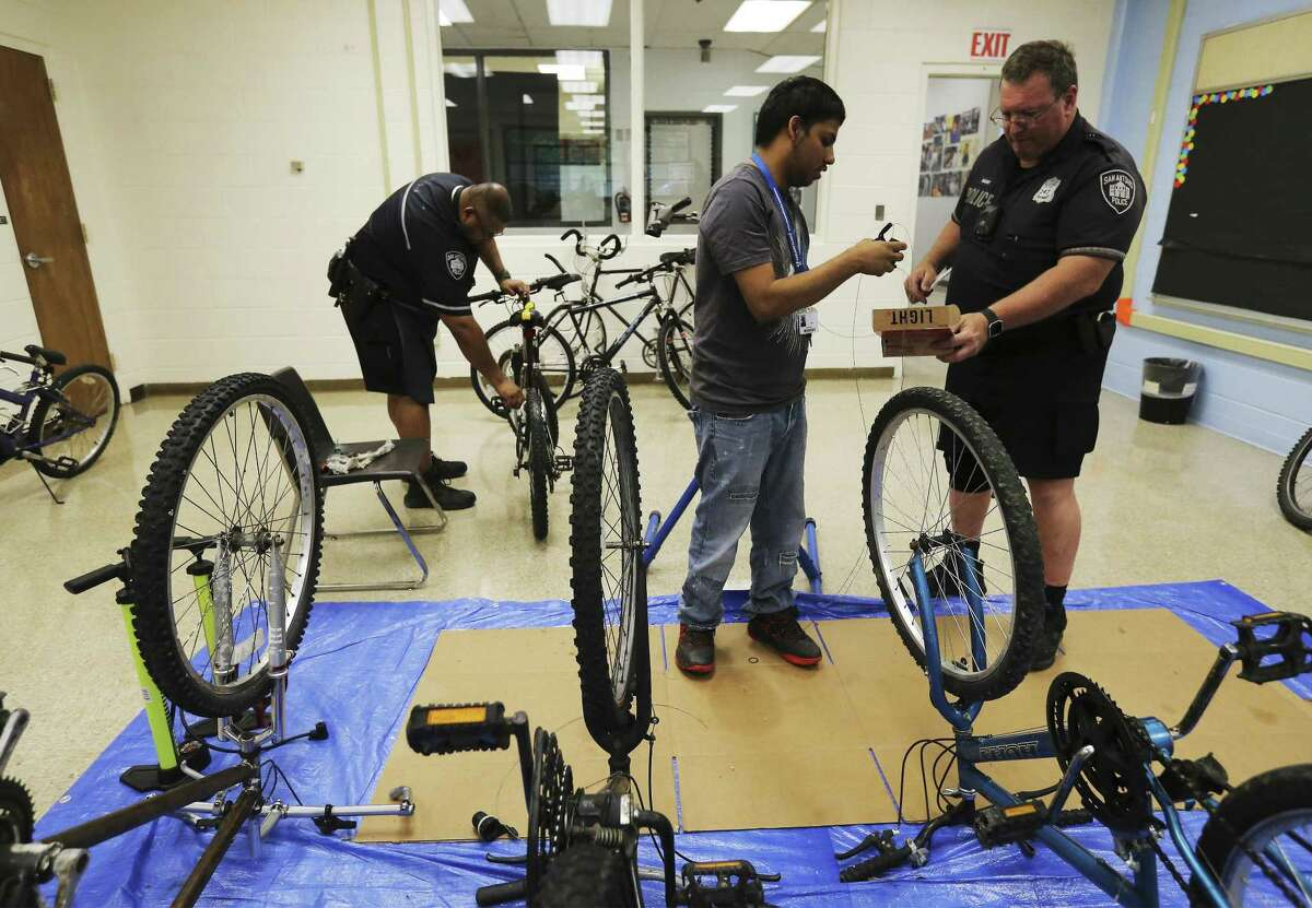 Justin Avila (center) helps SAPD Bike Patrol Officer Steve Bazany (right) put away parts as Edgewood ISD and San Antonio police partnership to teach special needs students how to rebuild and repair bicycles. For about the past four weeks at the Edgewood ISD Family Service Center, special needs individuals have been working with SAPD Bike Patrol officers Bazany and Ian Garcia in learning how to repair bicycle brakes, change out gears or fix a flat tire as part of the school district's 18-plus Transitional Program. The class is held twice a week for about 90 minutes. The bicycles are donated from the SAPD property room according to Bazany. The ultimate goal of the program is to help individuals with special needs to acquire job and life skills. (Kin Man Hui/San Antonio Express-News)