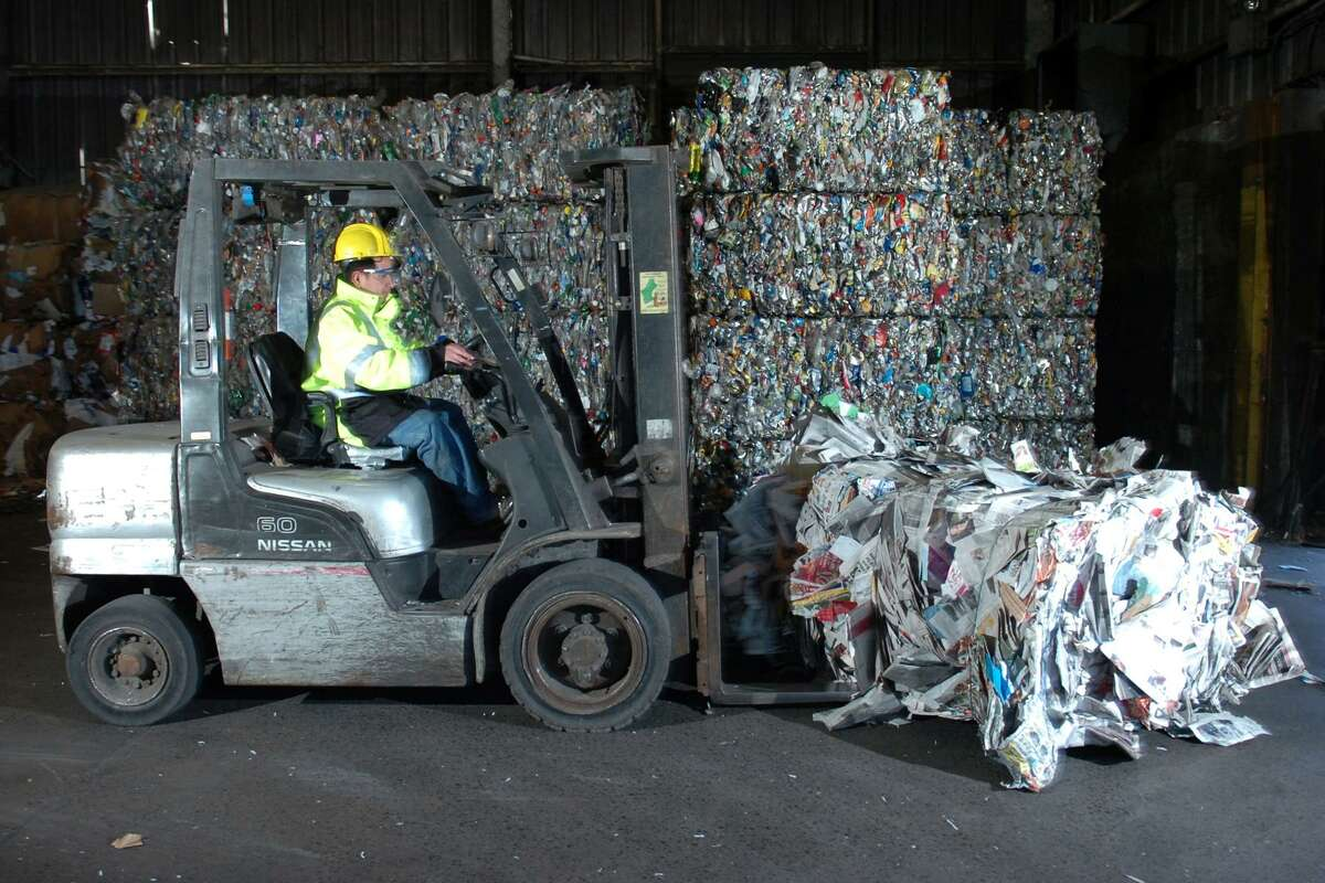 It's way past 1990 but here Nicholas Herrera drives a forklift load of bundled newsprint at Fairfield County Recycling Inc. in Stratford in 2010.