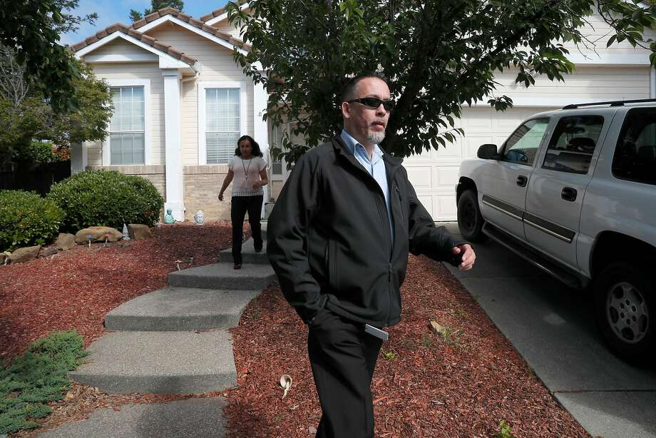 Two people from the Solano County Public Defender's Office leave the Fairfield home Tuesday where 10 children lived under allegedly abusive, neglectful and torturous conditions. Photo: Michael Macor / The Chronicle
