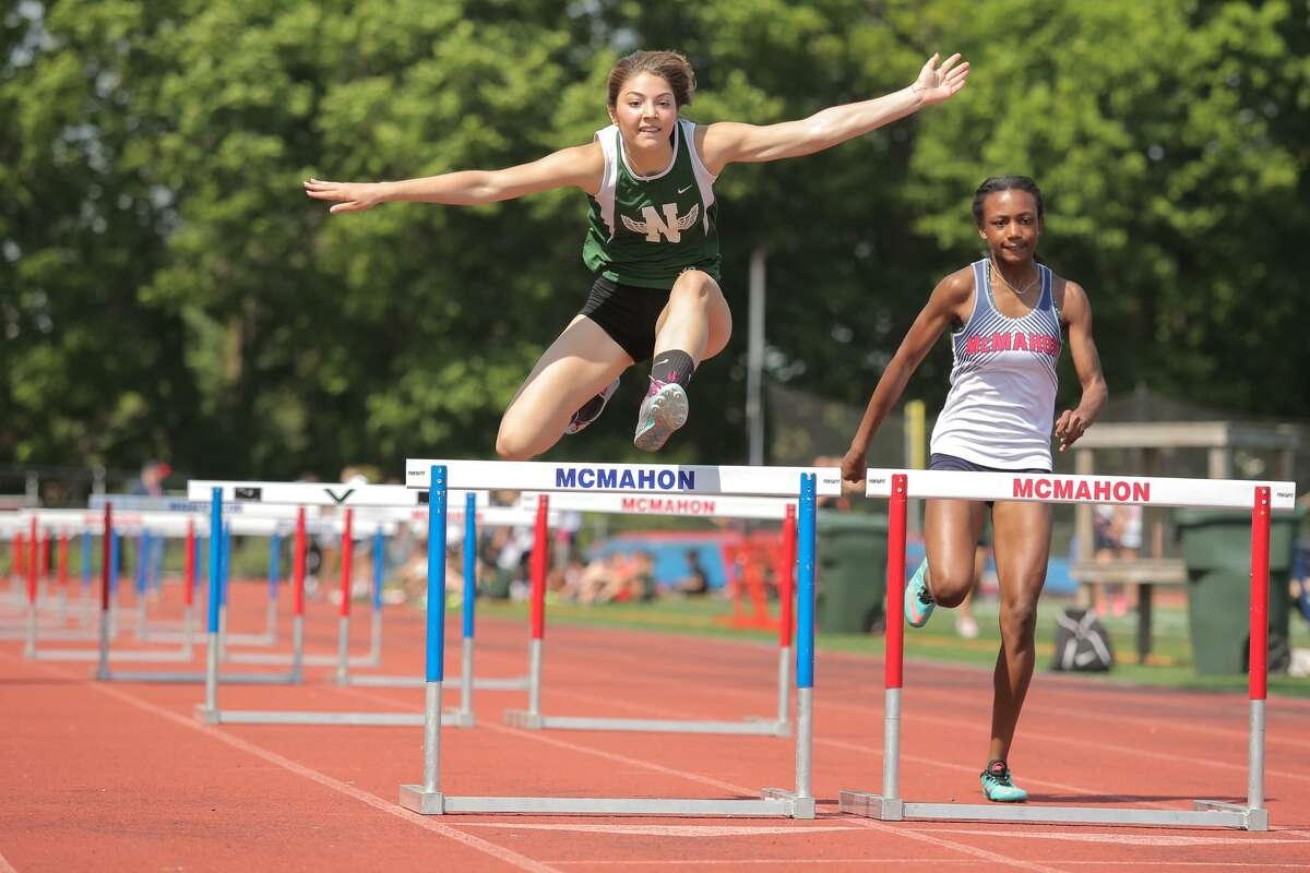 Norwalk's Lily Haden runs past McMahon's Liberty Brown in the hurdles during the Norwalk High and McMahon track meet Tuesday at Brien McMahon High School in Norwalk.