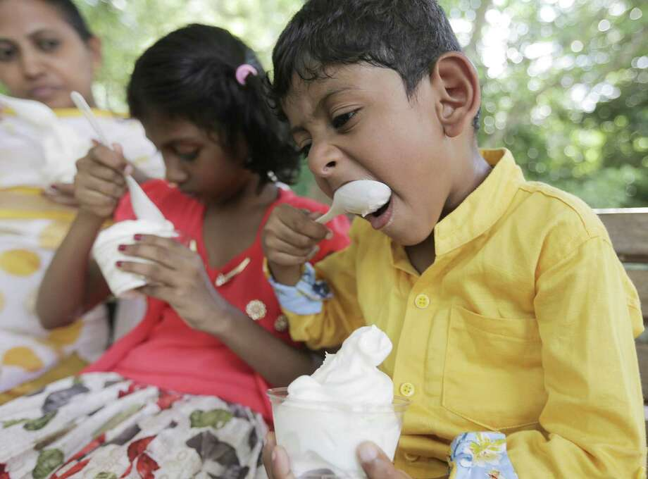Edric Burton Bose, 4, takes a big bite of ice cream with his sister, Minny Aislynn, 7, and mom, Anitha, at the Houston Zoo on Tuesday, May 15, 2018. The family lives in India, but are visiting over summer break with their father, Russel, who works in Houston. (Elizabeth Conley/Houston Chronicle) Photo: Elizabeth Conley, Chronicle / Houston Chronicle / ©2018 Houston Chronicle