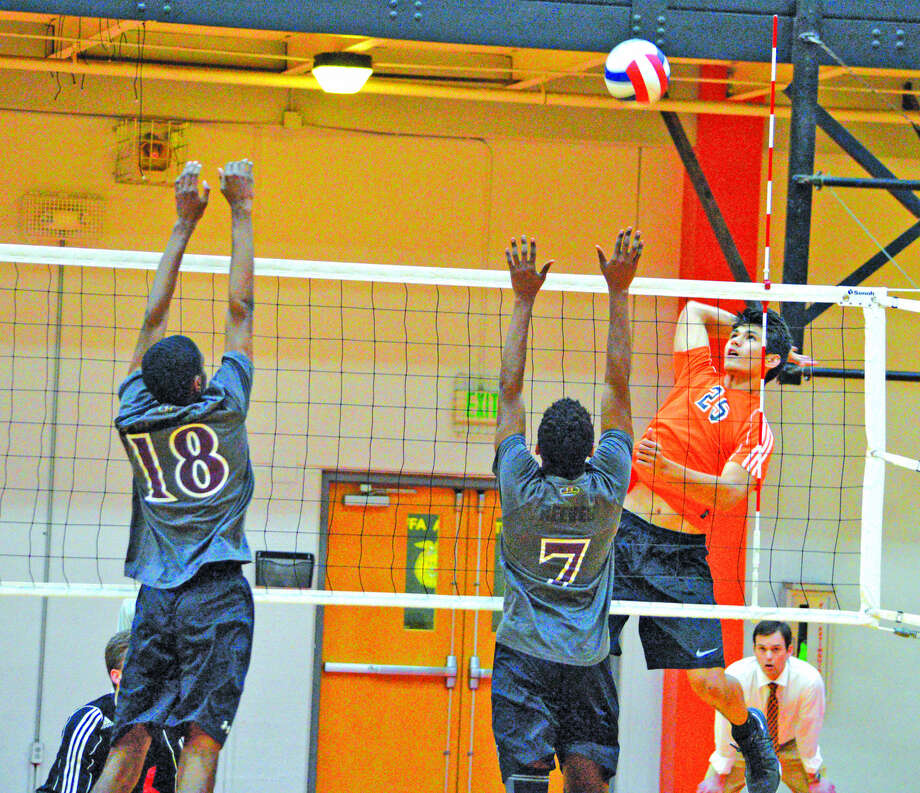 Edwardsville sophomore Eric Epenesa, right, goes up for a kill during the first game of Tuesday's Southwestern Conference match against Belleville West at Lucco-Jackson Gymnasium.