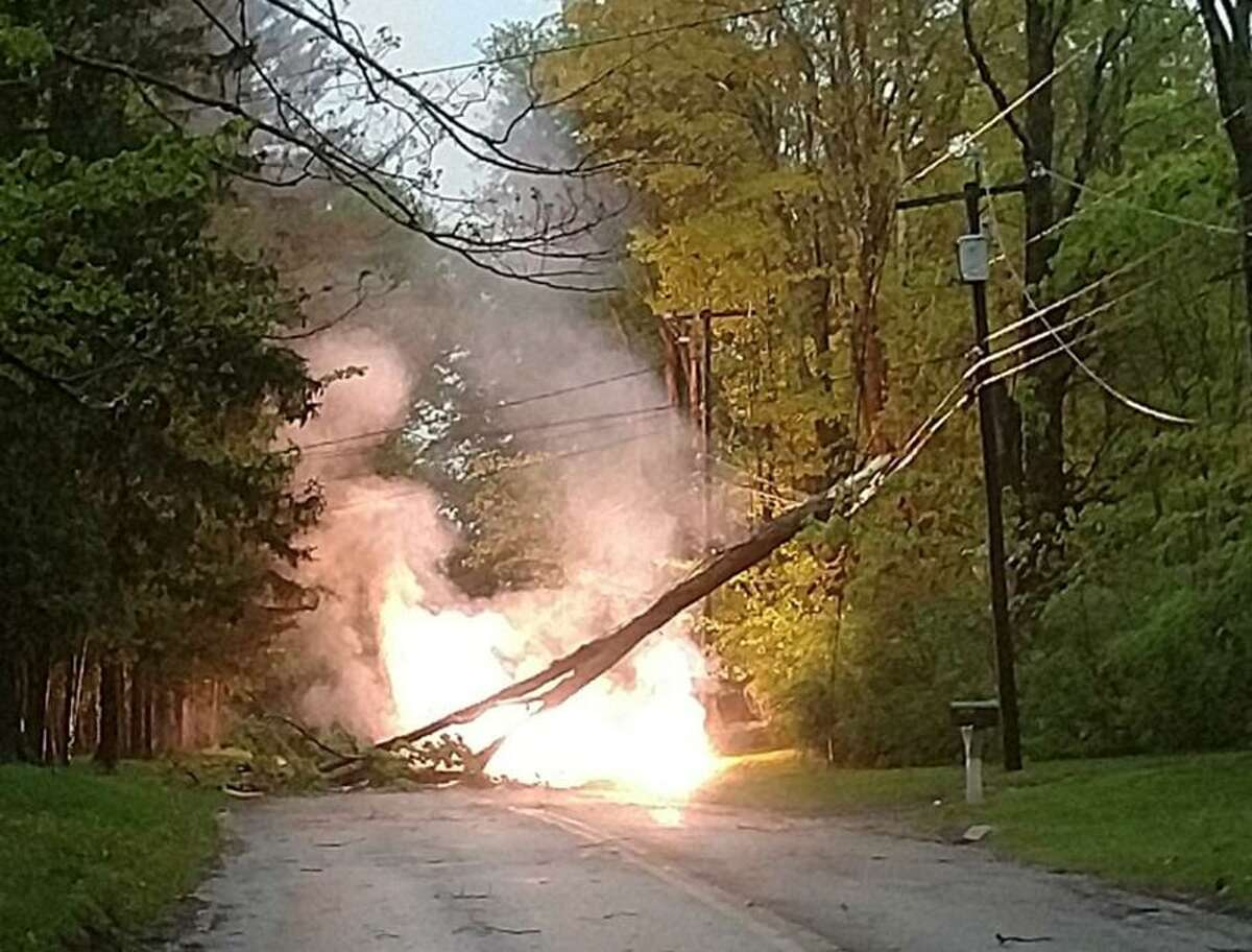 A fallen trre branch catches fire on powerlines in during Tuesday's storm, May 15, 2018.