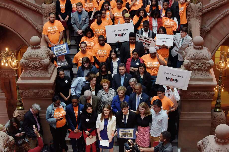 Surrounded by students and legislators, Rebecca Fischer, foreground center, executive director of New Yorkers Against Gun Violence, addresses those gathered for a rally inside the Capitol on Tuesday, May 15, 2018, in Albany, N.Y.  (Paul Buckowski/Times Union) / (Paul Buckowski/Times Union)