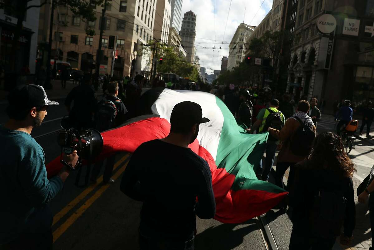 Palestinians march down Market Street during the