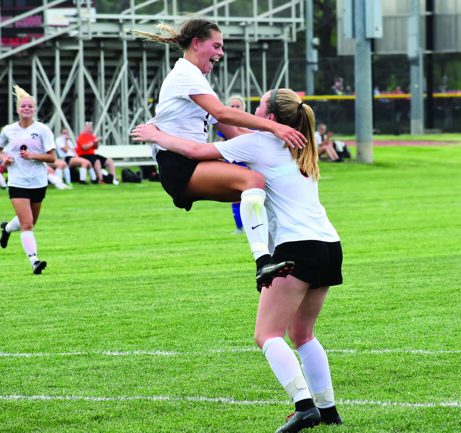 Edwardsville's Hannah Bielicke, left, jumps into the arms of teammate Paityn Schneider after scoring a goal in the first half of Tuesday's game.