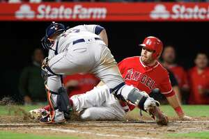 Los Angeles Angels' Ian Kinsler, right, is tagged out by Houston Astros catcher Brian McCann while trying to score on a single by Kole Calhoun during the seventh inning of a baseball game Tuesday, May 15, 2018, in Anaheim, Calif. (AP Photo/Jae C. Hong)