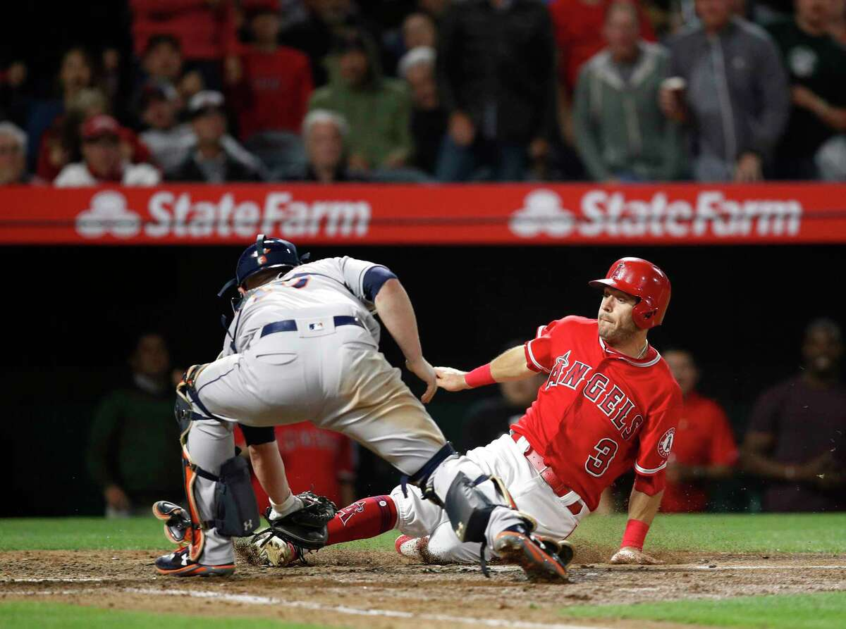 Los Angeles Angels' Ian Kinsler, right, is tagged out by Houston Astros catcher Brian McCann while trying to score on a single hit by Kole Calhoun during the seventh inning of a baseball game Tuesday, May 15, 2018, in Anaheim, Calif. (AP Photo/Jae C. Hong)