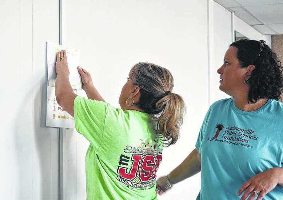 Lori Carr (left) and Amy Albers put up a planner Tuesday in their new office. Jacksonville School District 117 is moving its central office facilities from Jordan Street into a new space on State Street. Photo:       Audrey Clayton | Journal-Courier