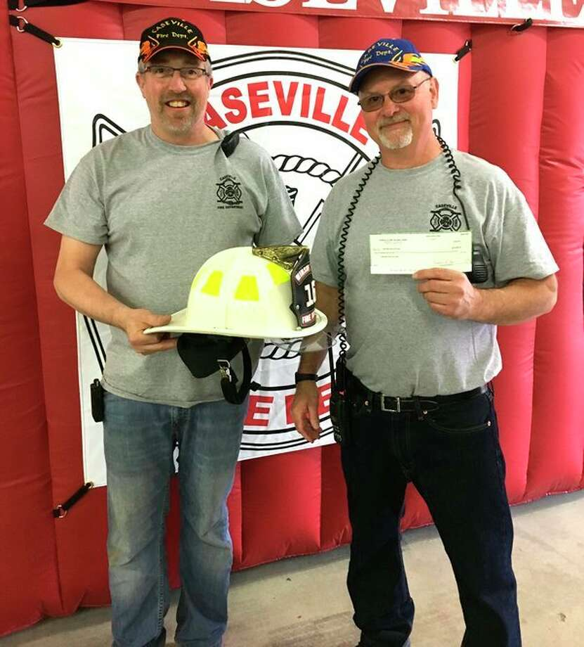 (Left) Assistant Fire Chief Carl Brunni and Fire Chief Ben Willenberg, of the Caseville Fire Department, display one of the new helmets that will be purchased with a check for $5,000 that they received from the Helping Hands Thrift Shop and the Caseville United Methodist Church. (Submitted to the Tribune)