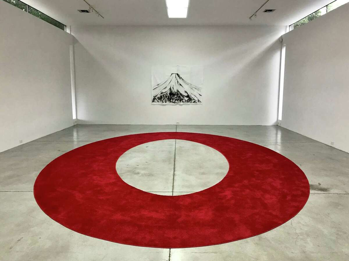 """""""I am a very important person,"""" a custom-designed red carpet, fills a floor below a charcoal drawing on felt of Mount Fuji in Ariane Roesch's solo show """"V.I.P."""" at Gallery Sonja Roesch through May 26."""
