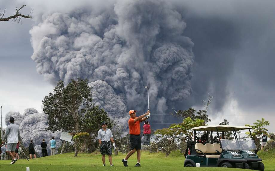 HAWAII VOLCANOES NATIONAL PARK, HI - MAY 15:  People play golf as an ash plume rises in the distance from the Kilauea volcano on Hawaii's Big Island on May 15, 2018 in Hawaii Volcanoes National Park, Hawaii. The U.S. Geological Survey said a recent lowering of the lava lake at the volcano's Halemaumau crater 'has raised the potential for explosive eruptions' at the volcano.  (Photo by Mario Tama/Getty Images) Photo: Mario Tama/Getty Images