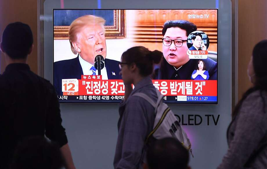 People walk past a television news screen showing North Korean leader Kim Jong Un (R) and US President Donald Trump (L) at a railway station in Seoul on May 16, 2018. North Korea threatened on May 16, to cancel the forthcoming summit between leader Kim Jong Un and President Donald Trump if Washington seeks to push Pyongyang into unilaterally giving up its nuclear arsenal. / AFP PHOTO / Jung Yeon-jeJUNG YEON-JE/AFP/Getty Images Photo: JUNG YEON-JE;Jung Yeon-je / AFP / Getty Images