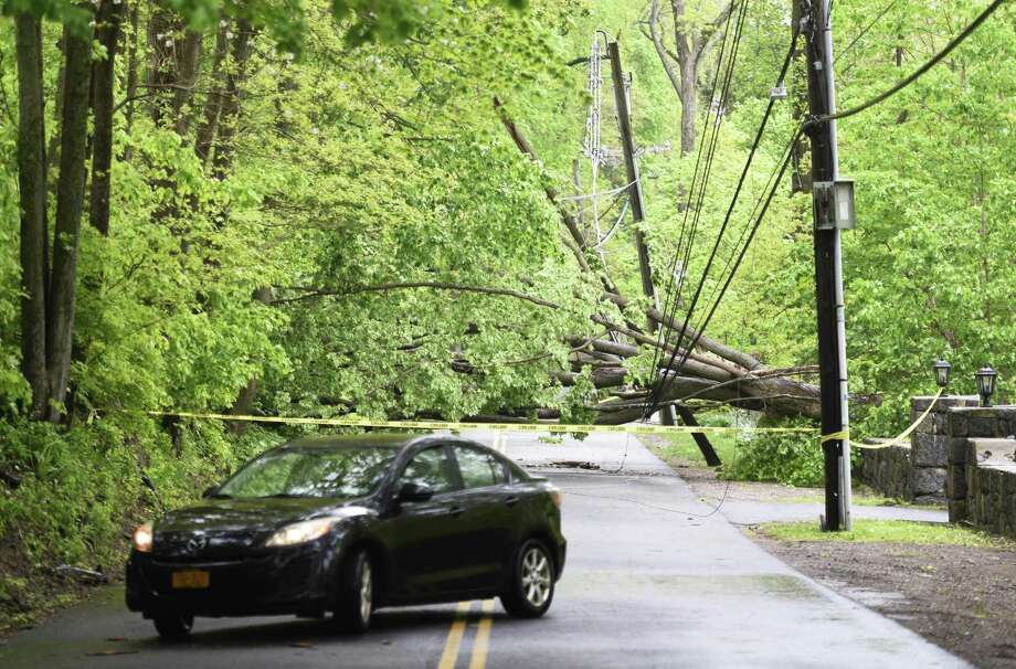 A large fallen tree blocks traffic from proceeding down Parsonage Road in Greenwich, Conn., Wednesday, May 16, 2018. Greenwich saw strong winds during Tuesday's storm, causing road closures and power outages throughout town. Photo: Tyler Sizemore / Hearst Connecticut Media / Greenwich Time