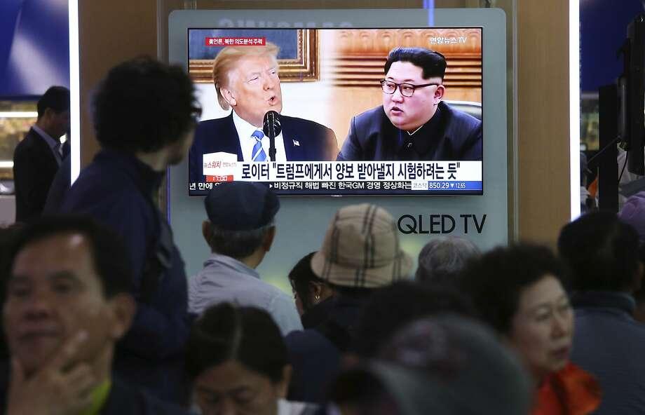Pedestrians in Seoul watch a program regarding the summit between President Trump and Kim Jong Un. Photo: Ahn Young-joon / Associated Press