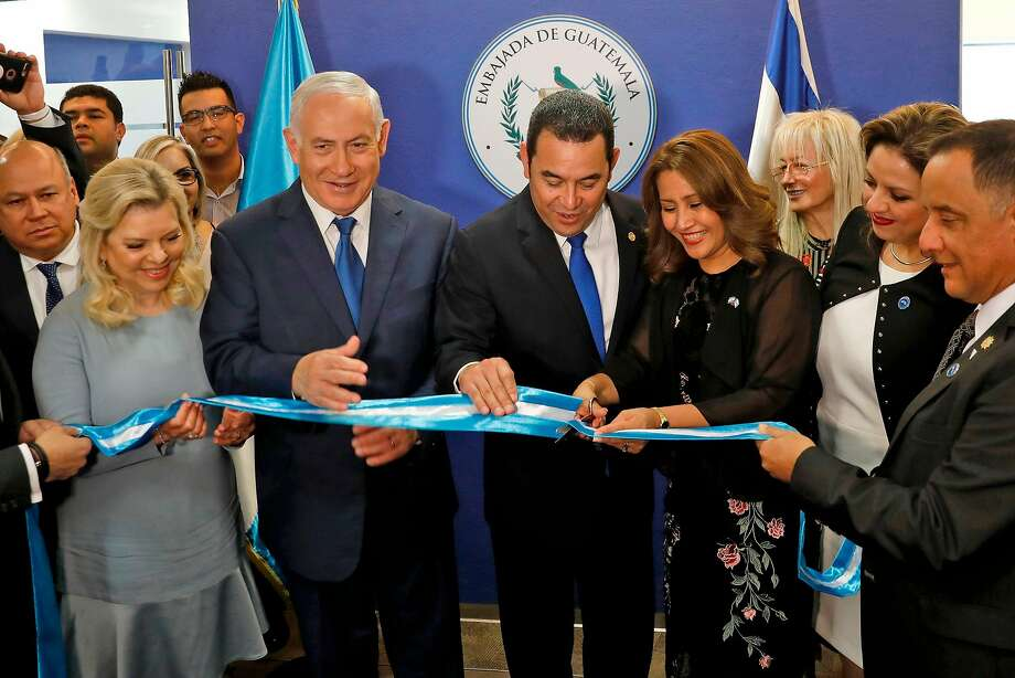 (Left to right) Sara Netanyahu and her husband Prime Minister Benjamin applaud Guatemala President Jimmy Morales and his wife at the inauguration of the Guatemalan embassy. Photo: RONEN ZVULUN;Ronen Zvulun / AFP / Getty Images