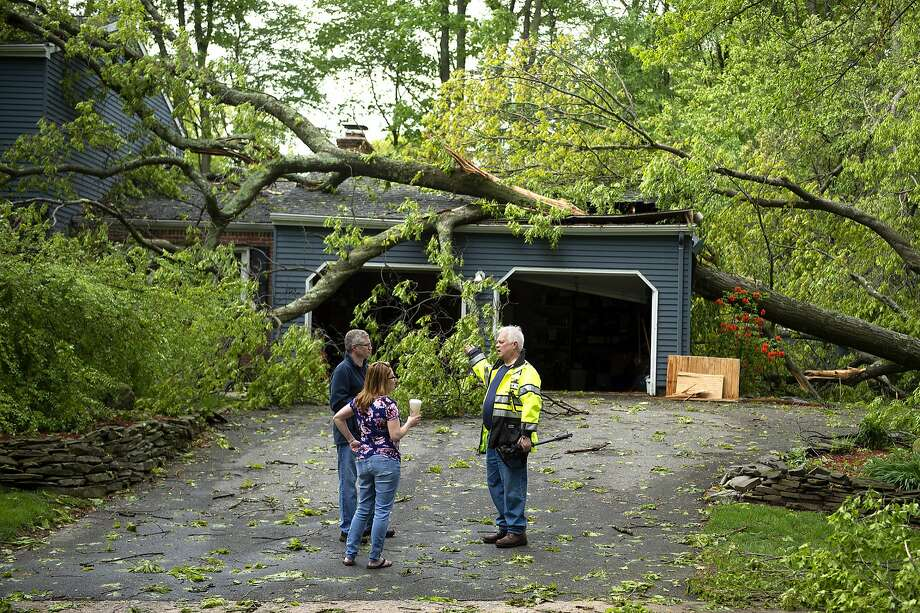 Chris Fletcher (left) and his wife Noel survey storm damage to their home in Cheshire Conn. with a volunteer firefighter a day after powerful rains pounded the region. Photo: Patrick Raycraft / Associated Press