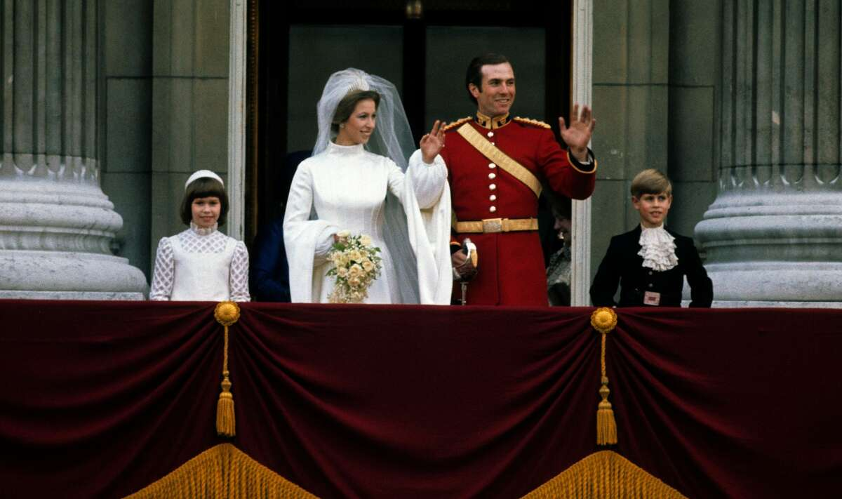 Princess Anne and Mark Phillips wave from the balcony of Buckingham Palace following their wedding on November 14, 1973 in London.