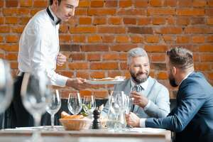 Two businessmen having lunch in the pub. Waiter serving pizza.
