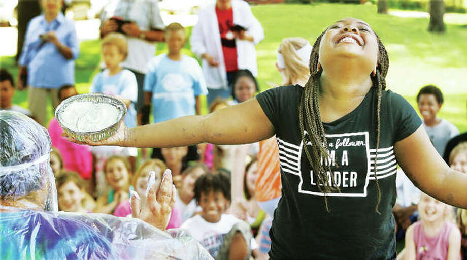 West Elementary School third-grade student Courtaysia Slack savors the moment Wednesday before slamming a cream pie into the face of her teacher, Amy Miller, left, on the school's front lawn. Students participating in the Accelerated Reading program were rewarded for reaching the goal for the first time ever in Miller's class. The class combined to read over 25 million words with a comprehension score of 92 percent, and at a level above their grade level. Photo:       John Badman | The Telegraph
