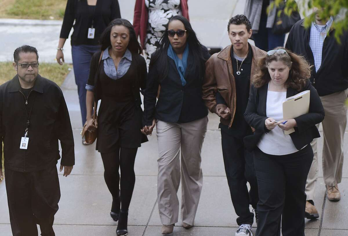 In this photo provided by the Daily Republic, Ina Rogers, center, walks to Solano County Superior Court in Fairfield, Calif., Wednesday, May 16, 2018, to face multiple charges of felony child abuse. Bail for a California mother of 10 children who officials say suffered long-term abuse was set at nearly $500,000 after the judge said she remains a danger to the kids. Prosecutors charged Rogers, 31, on Wednesday in Solano Superior Court with nine counts of felony child abuse, saying that she caused the children to be in a situation likely to produce great bodily injury and death. Her husband, Jonathan Allen, faces multiple charges of torture and felony child abuse. He has pleaded not guilty and remains in Solano County Jail on $5.2 million bail.