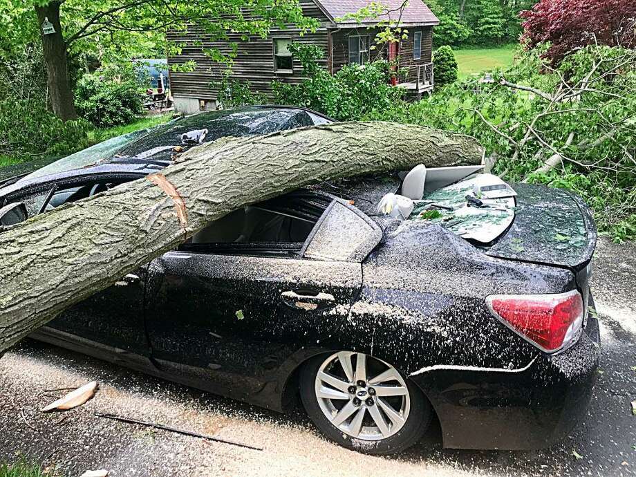 A giant maple toppled Tuesday evening, crushing the Willets family car, after a powerful thunderstorm ripped through Durham. It left downed trees, limbs and branches all across town. Photo: Cassandra Day / Hearst Media CT