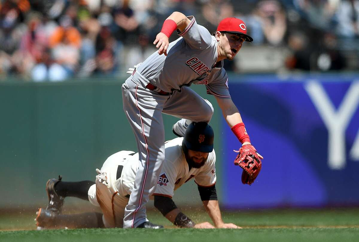 SAN FRANCISCO, CA - MAY 16: Scooter Gennett #3 of the Cincinnati Reds leaps over Brandon Belt #9 of the San Francisco Giants after getting his throw off to complete the douple play in the bottom of the fifth inning at AT&T Park on May 16, 2018 in San Francisco, California. (Photo by Thearon W. Henderson/Getty Images)