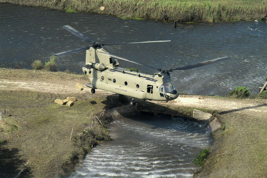 Hay bales are pushed from a Michigan Army National Guard Chinook helicopter in the Hamshire area on Monday. The bales were set to help feed an estimated 2,000 head of livestock stranded by Hurricane Harvey flood waters. Photo taken Monday, September 04, 2017  Guiseppe Barranco/The Enterprise Photo: Guiseppe Barranco, Photo Editor / Guiseppe Barranco ©