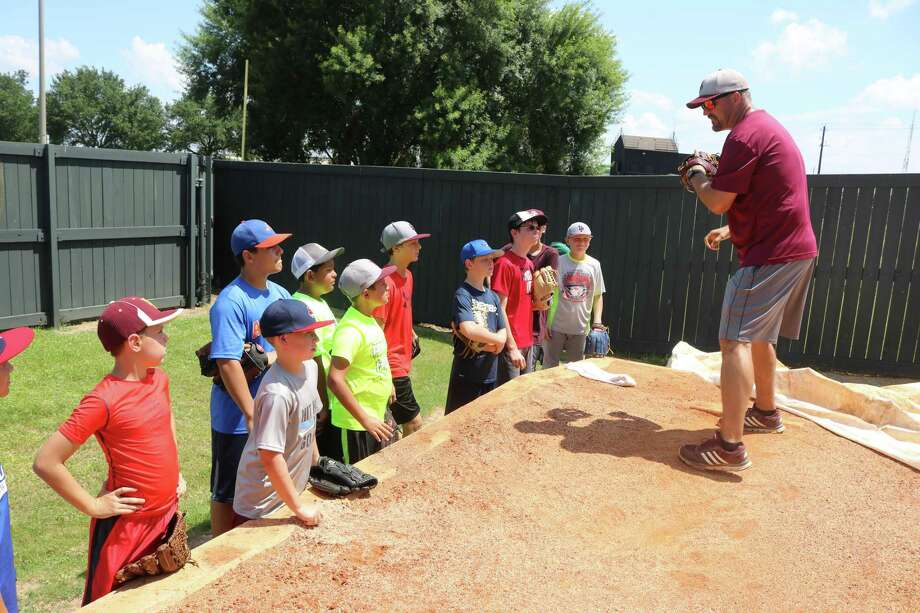 Kids listen intently to former San Diego Padres pitcher Donnie Elliott on how to improve their pitching during last year's camp. A Deer Park graduate, Elliott was first drafted by the Philadelphia Phillies. Photo: Robert Avery