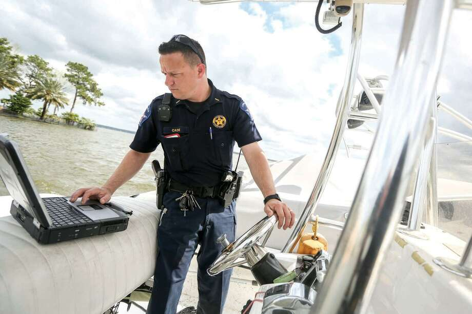 Lt. Tim Cade, with Montgomery County Pct. 1 Constable's Office Lake Division, looks up the information for a boat that was found drifting on Lake Conroe after water levels surged two feet above the maximum capacity on Friday, March 11, 2016. Photo: Michael Minasi, Photographer