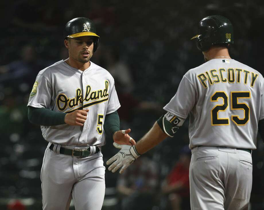 Oakland Athletics Jake Smolinski (5) is greeted by Stephen Piscotty (25) after scoring on a single by Jonathan Lucroy in the ninth inning of a baseball game against the Texas Rangers Monday, April 23, 2018, in Arlington, Texas. (AP Photo/Richard W. Rodriguez) Photo: Richard W. Rodriguez / Associated Press